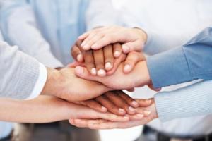 Tre mennesker legger hendene over hverandre.