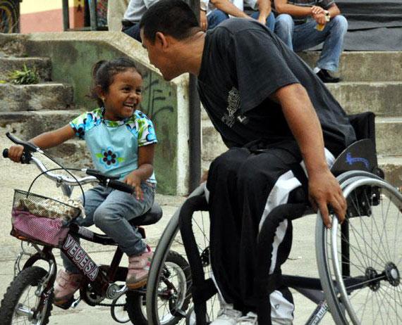 Mann i rullestol med ung pinke på sykkel