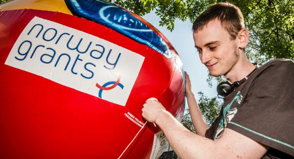 Ung mann med ballong merket Norway Grants