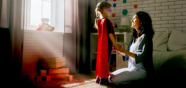 Ung jente med superhelt-drakt sammen med voksen kvinne i barneværelse